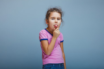 girl showing tongue on a gray background