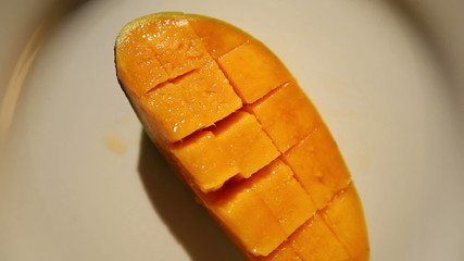 green mango half rotate on white plate