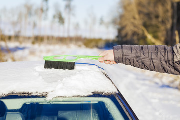 Man cleans with brush the car out of the snow