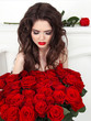 Beautiful brunette woman with red roses bouquet, valentines day.