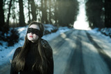 Girl with a blindfold on the background of gloomy road