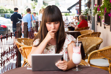 Sad girl in cafe with tablet
