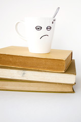 sleepy face cup on stack of books