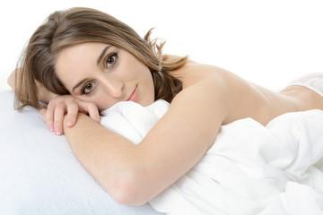 Hübsche Frau liegt entspannt im Bett