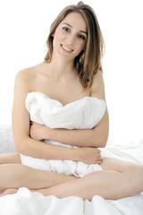 Teen sitzt auf Bett mit Decke