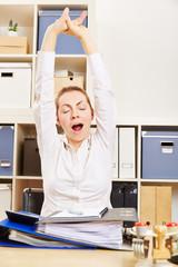 Müde Frau beim Gähnen im Büro