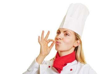 Köchin macht Zeichen für gutes Aroma mit Hand