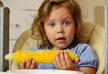 toddler girl eating corn