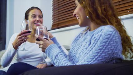 Two pretty women drinking wine in slow motion