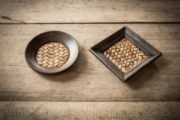 old bamboo coaster on wooden background
