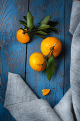 Two fresh mandarins with green leaves on wooden table