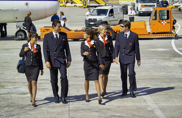 Italy, Olbia Airport, flight assistants near an airplane