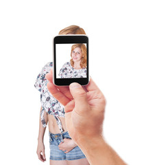 photographing smartphone beautiful girl in shorts on a white bac