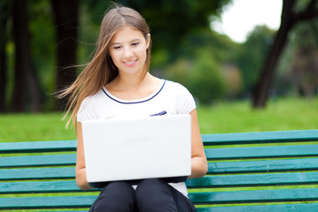 Young woman using a laptop at the park