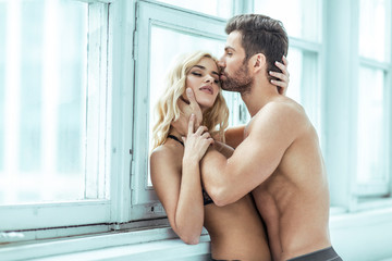 Handsome man kissing blond beauty
