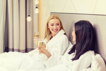 smiling girlfriends with champagne glasses in bed