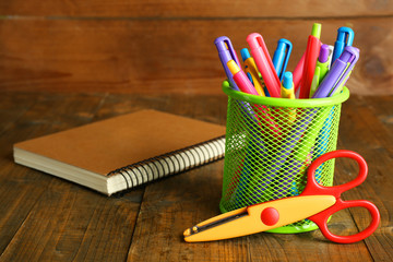 Metal holder with different pens, notebook and scissors