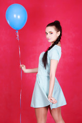 Portrait of a young attractive woman holding blue balloon