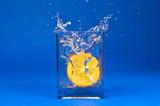 Water splash - orange persimmon fruit on blue background