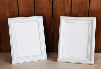 Photo frames on wooden surface and wooden wall background