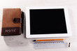 Tablet PC with notebook on wooden table background