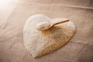 Rice laid out in a heart shape on sackcloth with wooden spoon