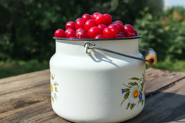 Cherries in white metal cans on a wooden table