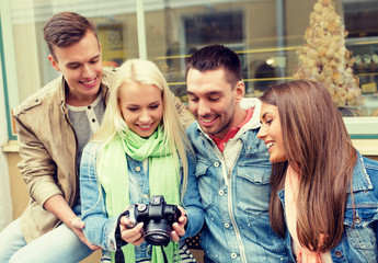 group of smiling friends with digital photocamera