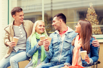 group of smiling friends with take away coffee