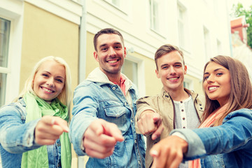 group of smiling friends in city pointing finger