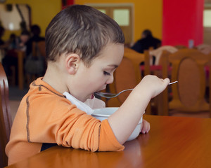 Child eating soup in restaurant