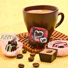 Cup of cappuccino with chocolate sweets and coffee beans