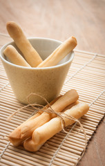 Breadsticks in napkin on wooden background.