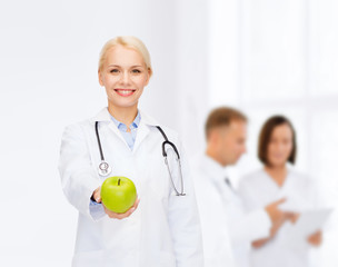 smiling female doctor with green apple