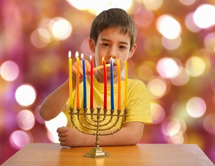 Israeli boy lighting a Hannukah Menorah