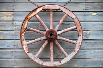 Old used wooden wheel hanging on rural wall