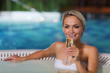 happy woman drinking champagne at swimming pool