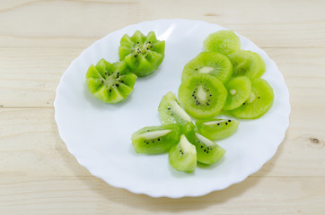 Sliced kiwi placed on a white plate