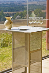 Four empty wine glasses on a table under the sun