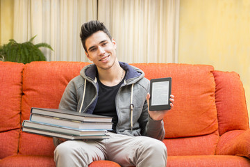 Young man showing difference between ebook reader and heavy