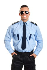 Smiling young policeman in sunglasses with his hands in pockets