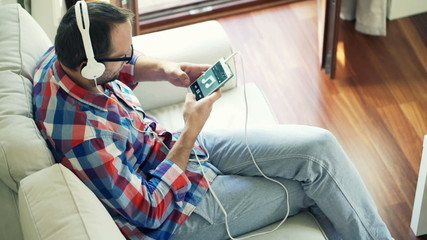 Young man listening to music on cellphone sitting on sofa