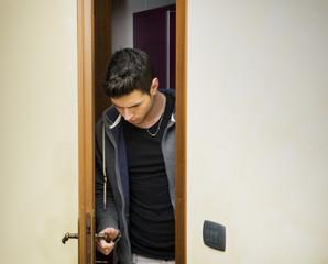 Handsome young man opening door to enter