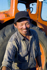 Mongolian Farmer Standing In Front Of His Tractor Reaching Forwa