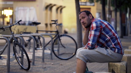 Young, sad man sitting in city during evening