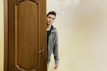 Handsome young man behind open door, getting out
