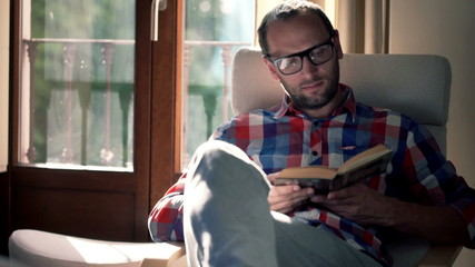 Portrait of happy man reading book sitting on chair at home