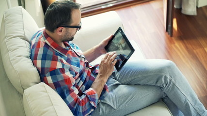 Man browsing photos on tablet computer sitting on sofa at home