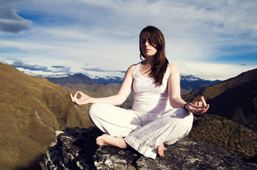Young Woman Meditating in the Wilderness with Beautiful Mountain