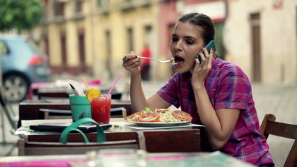 Beautiful woman talking on cellphone and eating salad in cafe